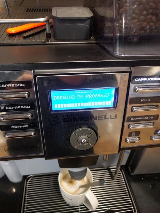 Coffee streaming into a mug from a coffee machine.