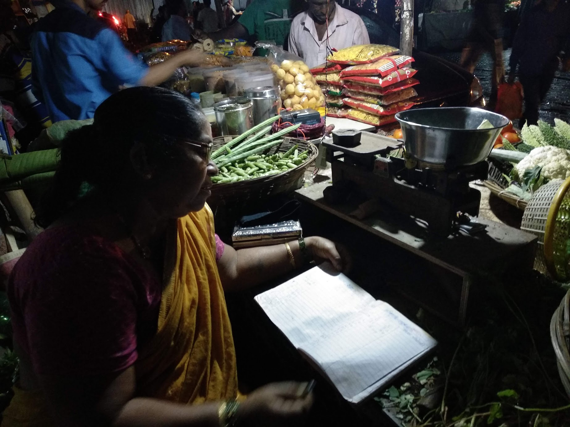 Vegetable vendor showing her notebook of accounts.""